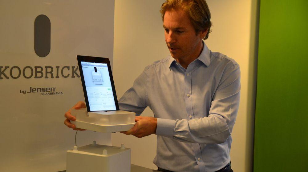 I hendene holder Karsten Kjoss Koobrick Docki (med iPad mini) og Koobrick Wifi, som han nettopp har løftet opp fra lagringsenheten Koobrick Boxi. Merk «Lego-knaggene» øverst på Boxi som gjør stabelen stabil.
