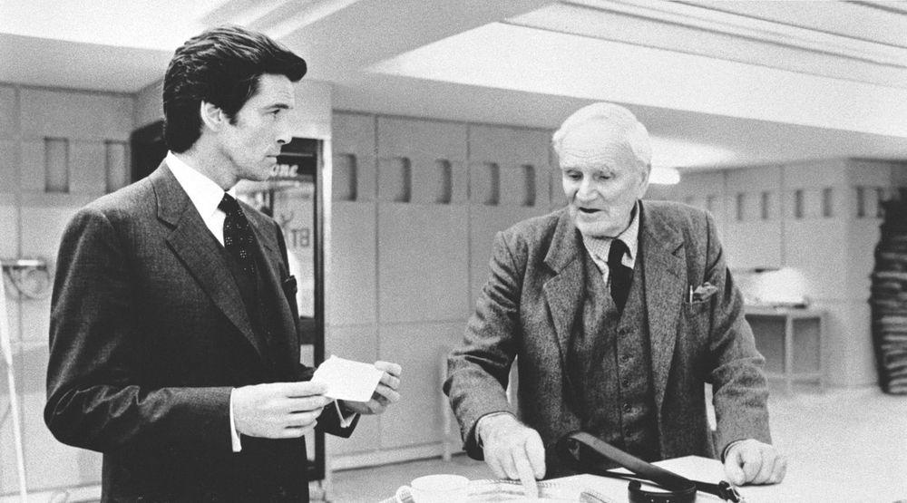 James Bond (Pierce Brosnan) sammen med sin hoffleverandør av teknologi, Q fra en scene fra Tomorrow  Never Dies. Ifølge New York Times ville Q likt de nå avslørte kapasitetene til NSA.