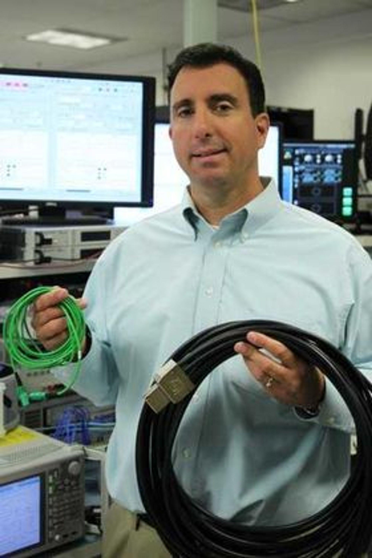 Mario Paniccia  med en 1,6 terabit per sekund MXC-kabel (grønn) og en kobberbasert 128 gigabit per sekund PCI Express-kabel.
