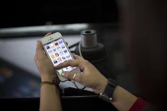En indisk kvinne prøver iPhone 5 i Mumbai. Til høsten kan det komme en billigere utgave av iPhone, som vil kunne gjøre innhugg i viktige asiatiske markeder.