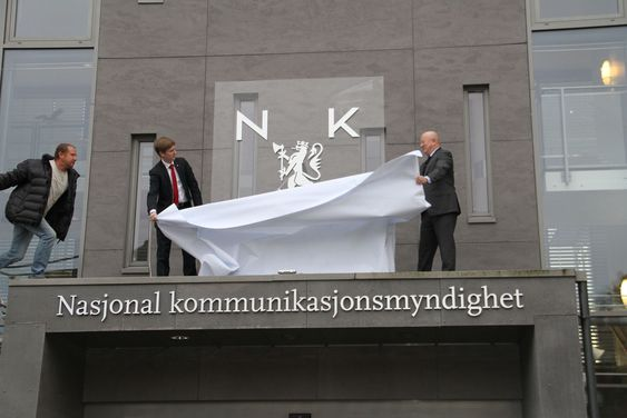 Politisk rådgiver Reynir Jóhannesson i Samferdselsdepartementet og Nkom-direktør Torstein Olsen (t.h.) avduket det nye etatsmerket ved hovedkontoret i Lillesand mandag. (Til venstre en hjelpende hånd fra lift-operatør Kurt Værholm.
