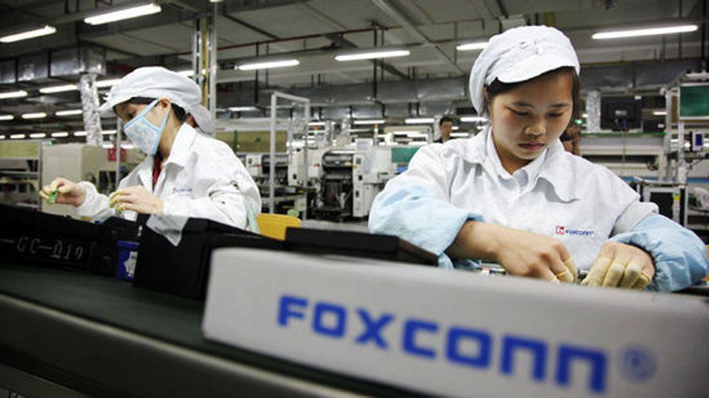 Arbeidere ved samlebåndet i en Foxconn-fabrikk i Kina som produserer iPhone.