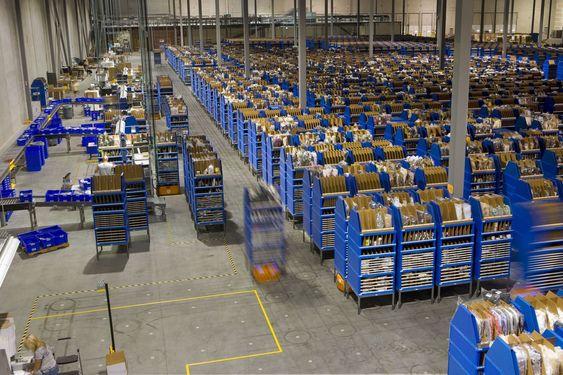 """I stedet for at lagerarbeidere flyr mellom reolene, sørger Kiva-robotene for at det er lagerhyllene som """"flyr""""."""