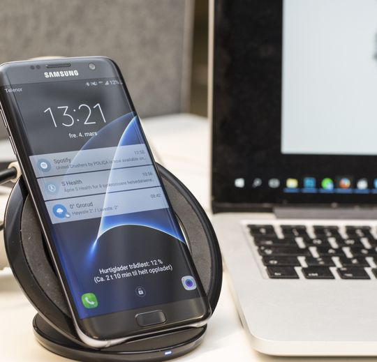Galaxy S7 Edge hurtiglader ved siden av PC-en.