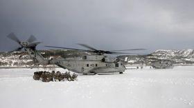 Nederlandske marineinfanterister sitter i kringvern på bakken når to amerikanske CH-53E tar av under vinterøvelsen Cold Response 2016.