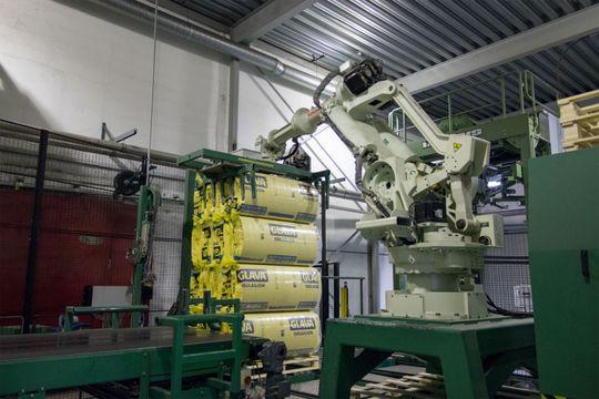 Fem pakker Glava til én pakke som komprimeres ytterligere, før en stor robotarm laster pakkene på en pall.