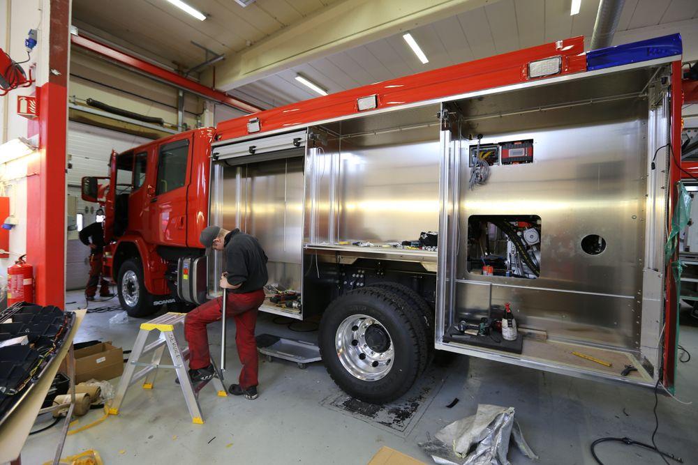 To personer jobber sammen på hver brannbil.