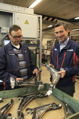 Hans Petter Kristiansen (t.v.) med ferdig montert hjuloppheng til Volvos XC 90-serie. Christopher M. Braathen med delen før den sendes inn i den robotiserte monteringslinjen.