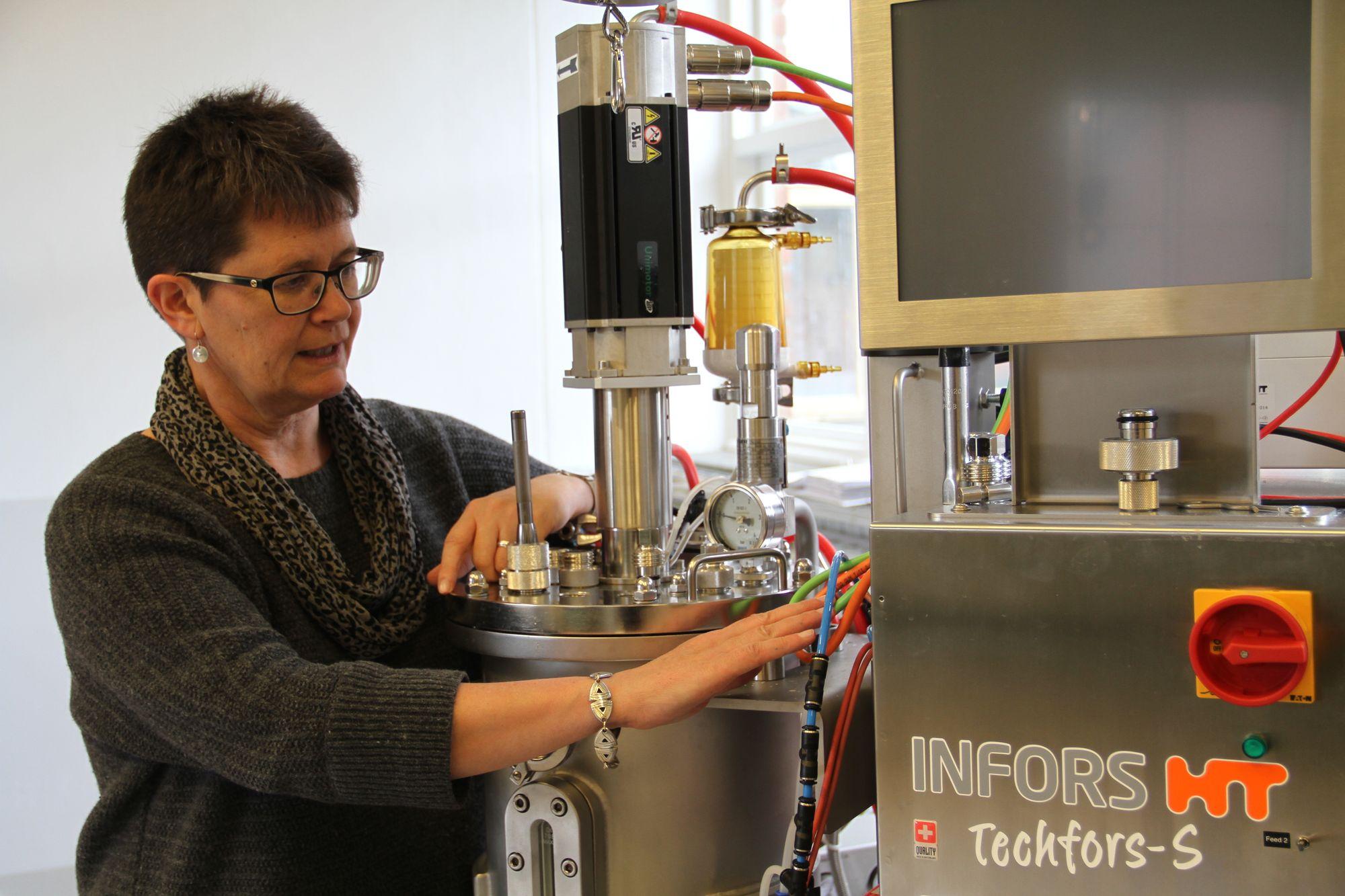 Professor Margareth Øverland ved en av de nyinnkjøpte bioreaktorene som brukes til å lage enzymer og gjær som proteinkilde. Foto: Joachim Seehusen.