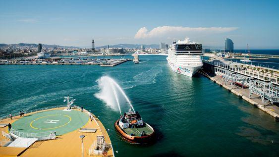Taubåter hilser det nye cruiseskipet med å sende kaskader av vann opp i lufta ved avgang fra Barcelona.