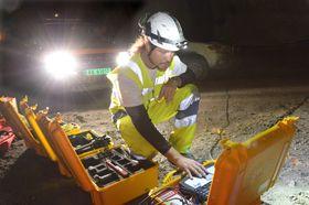 Jozset Hecht Mendez fra Amberg Technologies sjekker målingene som er tatt i fjellet i Hundvågtunnelen. .