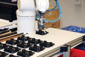 KA Raufoss har fått hjelp av Sintef Manufacturing til å skreddersy automatisert fabrikasjon og montasje. Manifolder flyttet fra matebånd til en mellomstasjon der de blir stilt på skrå. Roboten kan dermed gripe dem uten å blokkere hullene for bremserørskoblingene.
