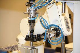 Robot plasserer bremserørskobling i hus, holdt av en annen robot ved Kongsberg Automotive Raufoss.