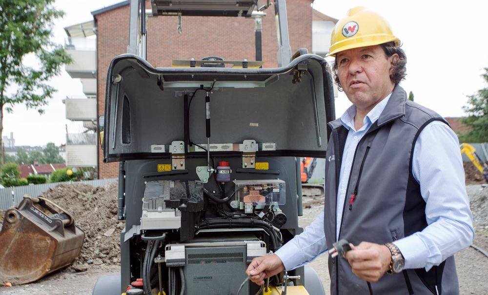 Jan Gunnar Halstvedt viser hvor batteriet plugges inn når anleggsmaskinen skal lades.