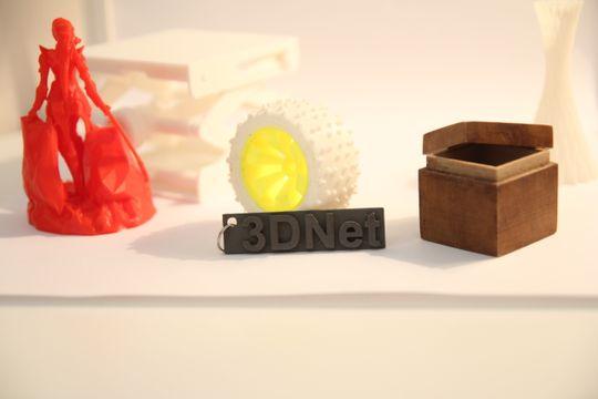 Ulike eksempler på 3D-skrevneobjekter. Et hjul til en RC-bil, klart for montering. Det lille skiltet med 3Dnet-logoen er laget med et filament som består av 30 prosent rustfritt stål. Den lille boksen kjennes ut som om den er av tre, og filamentet består da også av 30 prosent trevirke.