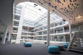 Trendy dynamikk: Store lounge-områder skal oppmuntre til spontan utveksling av ideer og informasjon. Store konferanserom har glassfasader mot atriet.