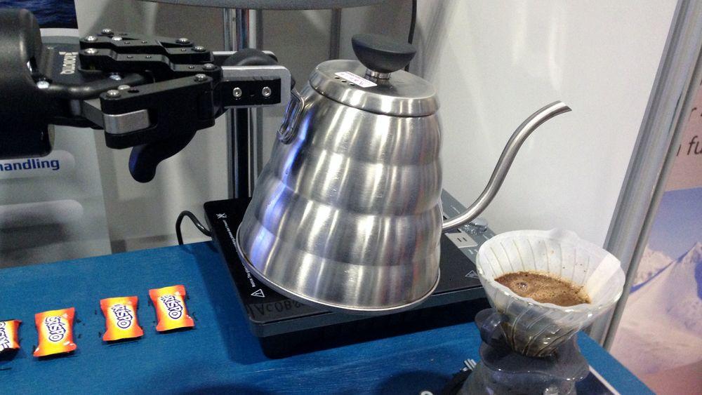 Roboten i gang med å helle kokende vann over nykvernet kaffe.