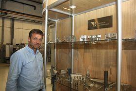 Salgsdirektør Runar Nordby, Tronrud Engineering, foran skryteutstilligen med ulike produkter i titan og andre materialer.