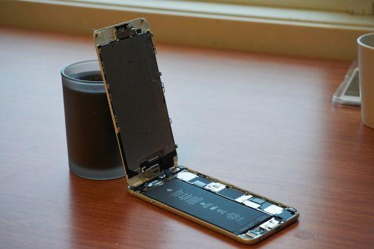 Alle iPhone-er av nyere generasjoner åpnes på denne måten. At skjermen kun er festet med et par kabler i toppen er av stor betydning for hvor enkelt og kostbart det kan bli å reparere telefonen.