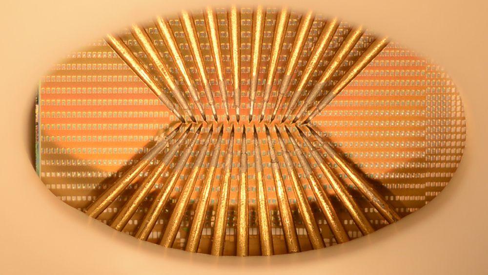 Bildet brikke med en stor matrise av faseskiftenheter, delvis dekket av et sett med spisse sonder som blant annet brukes til nøyaktig karakterisering og modellering. De mange små kvadratene er kontaktpunkter som er knyttet til de nanometerstore faseskiftcellene.