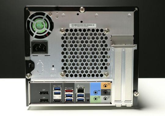 Baksiden av Shuttle SZ170R8, med den lille PSU-vifta oppe til venstre. På høyre side ser vi de avtagbare skinnene som gjør plass til et grafikkort eller annet tilleggskort. På hovedkortet i bunnen har vi to DisplayPort-kontakter, en HDMI 1.4, gigabit LAN, seks USB 3.0, en eSATA-port og minijacker for lyd.