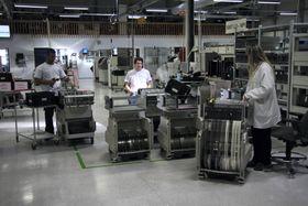 Kassetter med komponentene som skal monteres på kretskort gjøres klar før de settes inn i den automatiske produksjonslinjen.