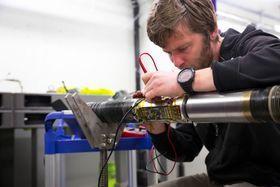 Tester: Softwareutvikler Simen Didden Dovland sjekker elektronikken før nok en runde med høy vibrasjons- og sjokktesting. Utstyret testes til det ødelegges, så de skal vite hvor grensen går.
