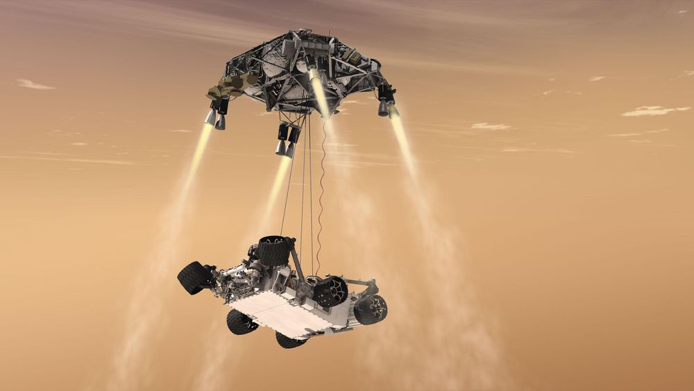 Landing i liner:  Illustrasjon av Sky Crane-konseptet under landingen av Curiosity i Gale-krateret på Mars 6. august 2012 – roveren blir senket til overflaten fra rakettplattformen i en høyde av 7,5 meter ved hjelp av tre nylonliner. Mars 2020 vil bruke det samme konseptet.