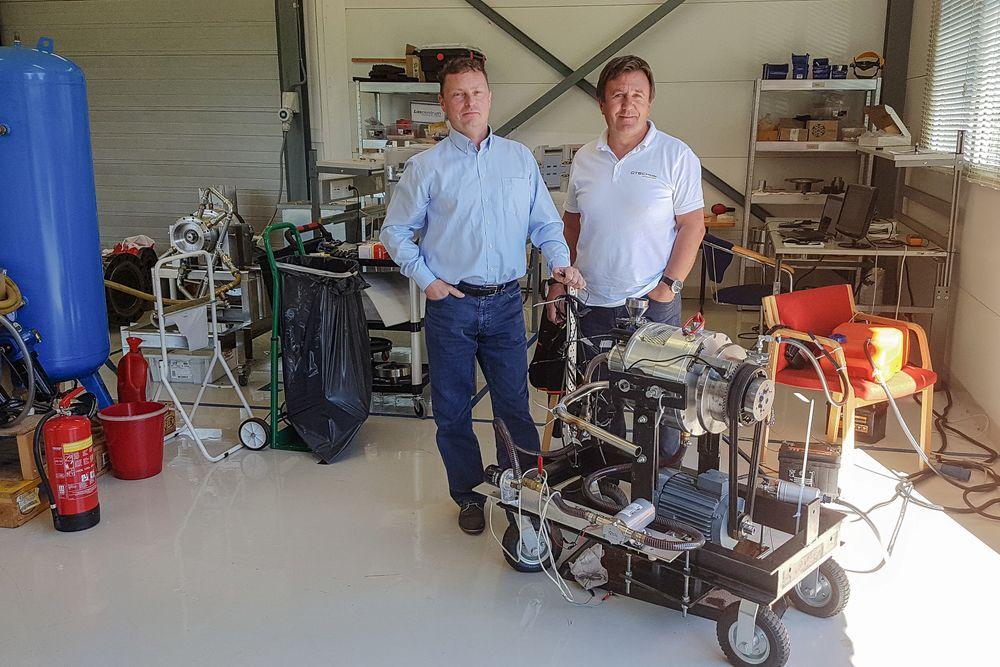 Motoren: adm. direktør i Otechos, Tor Arne Hauge (t.h.) og daglig leder, Frode H. Larssen vider frem motoren som er temmelig sliten etter utallige timer i testbenken. Selv om dette er den første prototypen yter den lille motoren 25o hester med sine 1,1 liter. Her er det stort potensial for forbedringer mener de to som nå skal sende motoren til Birmingham for ytterligere testing.