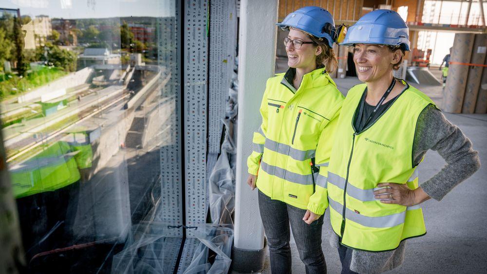 Magnhild Kallhovd og Bodil Motzke i Undervisningsbygg ser ut av vinduet fra flerbrukshallen på Brynseng skole som her var under oppføring. Nå håper de å ha løst problemet med overskuddstrømmen ved skolen.