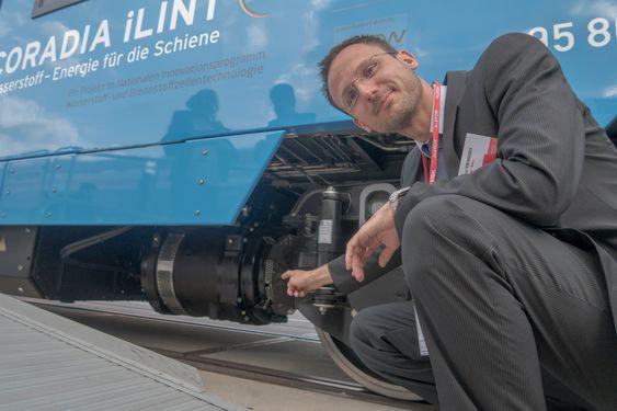 Konrad Steindorff er sjefingeniør med ansvar for fremdrift og brenselcellesystemet og peker på den elektriske asynkrone motoren som har erstattet dieselmotoren i det nye hydrogentoget.