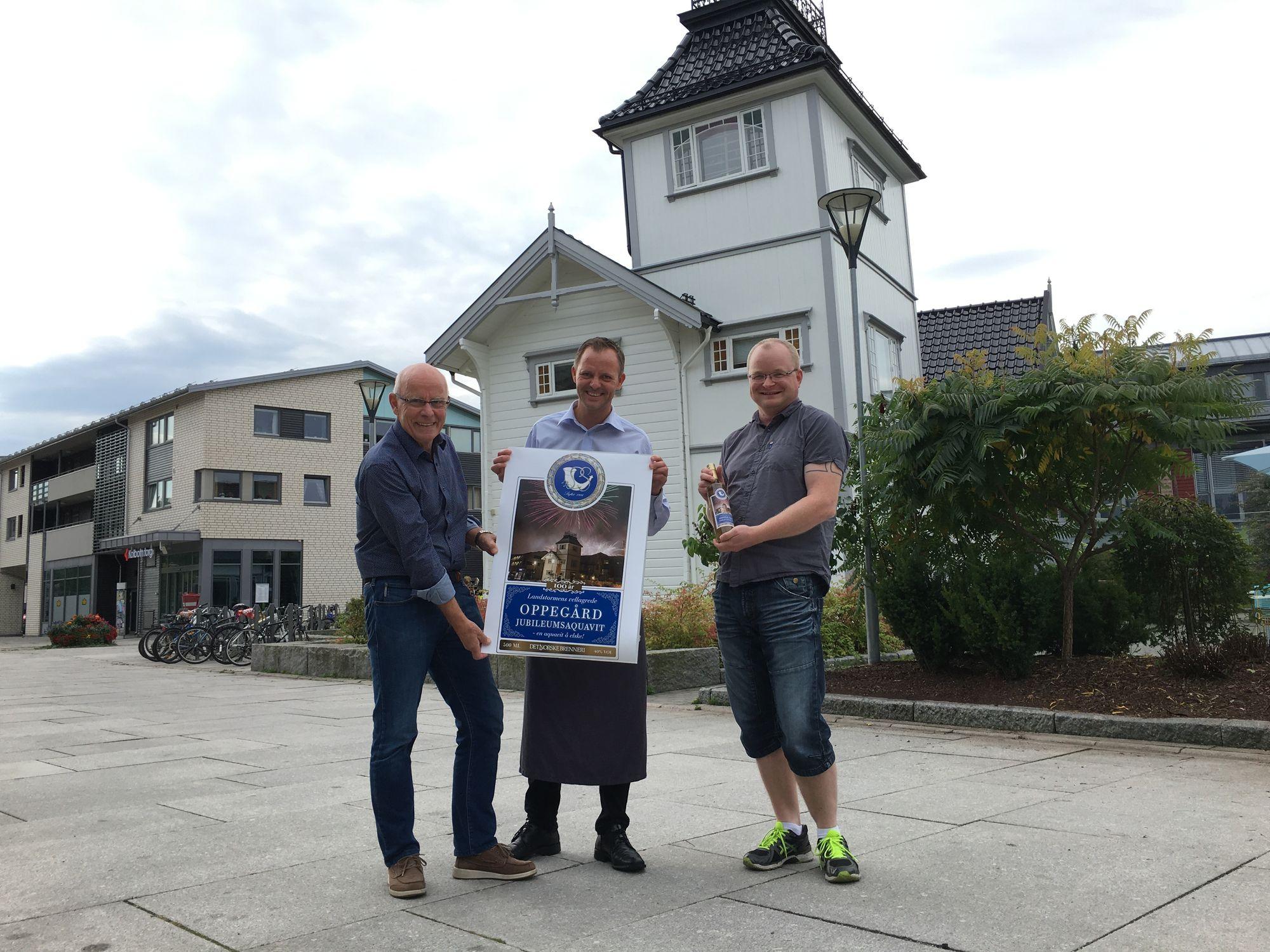 STOLTE: Torleif Bjøntegaard i Landstormen (t.v.), Vebjørn Aarflot fra Tårnhuset og fotograf Thomas Telstø Hysvær viser frem etiketten på Oppegård-akevitten.