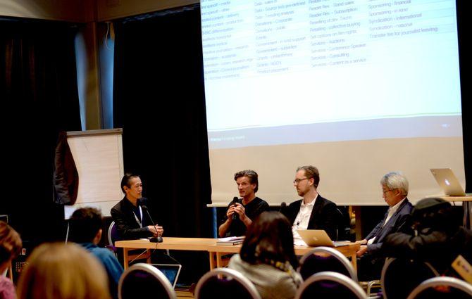 Panelet diskuterer non-profit og forretningsmodeller. På lerretet: Noen av de 52 måtene å finansiere journalistikk på.