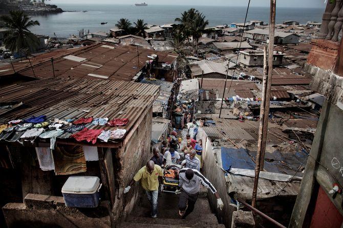 00619 2. Nyhet reportasje 21.01.2015 01/08 Ebola Et ambulanseteam bærer en mann de mistenker har ebola ut av slummen ved markedet i Freetown, Sierra Leone.  Hjelpearbeidere har kjempet mot ebolaviruset siden utbruddet av det i mai 2014. Mer enn 100 helsearbeidere og 11 av Sierra Leones rundt 120 leger har omkommet. Totalt er mer enn 3.500 mennesker døde av ebola i landet i januar 2015. I løpet av året klarte man å bekjempe virsuset ved blant annet å isolere smittede landsbyer, drive helsekampanjer, stenge grenseoverganger og i siste liten kom det internasjonale samfunnet på banen med både helsehjelp og økonomisk støtte.