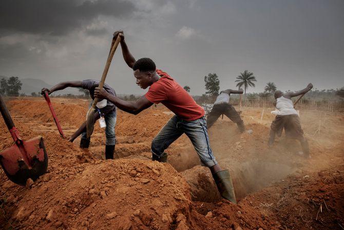 00619 2. Nyhet reportasje 20.01.2015 02/08 Ebola Unge menn jobber med å lage graver på en gigantisk kirkegård i utkanten av hovedstaden Freetown. Hver dag ankommer en rekke ambulanser med døde mennesker, alle pakket i gummi og sprayet med klorin for å hindre smitte. Ikke alle som gravlegges er døde av ebola, men alle behandles som om de har viruset for å hindre smitte. De unge mennene forbereder 12 nye graver uten beskyttelsesutstyr. Hjelpearbeidere har kjempet mot ebolaviruset siden utbruddet av det i mai 2014. Mer enn 100 helsearbeidere og 11 av Sierra Leones rundt 120 leger har omkommet. Totalt er mer enn 3.500 mennesker døde av ebola i landet i januar 2015. I løpet av året klarte man å bekjempe virsuset ved blant annet å isolere smittede landsbyer, drive helsekampanjer, stenge grenseoverganger og i siste liten kom det internasjonale samfunnet på banen med både helsehjelp og økonomisk støtte.