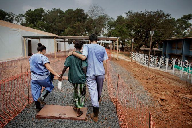 00619 2. Nyhet reportasje 20.01.2015 06/08 Ebola En pasient på ebolaklinikken drevet av Leger Uten Grenser i Freetown, Sierra Leone, går ut av leiren sammen med internasjonale helsearbeidere. Hun har overlevd ebolaviruset og kan få reise hjem. For første gang på lenge kan hun berøres ut totalt beskyttelsesutstyr. Hjelpearbeidere har kjempet mot ebolaviruset siden utbruddet av det i mai 2014. Mer enn 100 helsearbeidere og 11 av Sierra Leones rundt 120 leger har omkommet. Totalt er mer enn 3.500 mennesker døde av ebola i landet i januar 2015. I løpet av året klarte man å bekjempe virsuset ved blant annet å isolere smittede landsbyer, drive helsekampanjer, stenge grenseoverganger og i siste liten kom det internasjonale samfunnet på banen med både helsehjelp og økonomisk støtte.