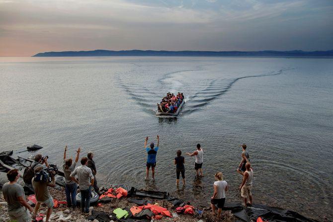 Presse, frivillige og lokale tar imot syriske flyktninger i en gummibåt når den ankommer de nordlige strendene på den greske øya Lesbos. Det er stort sett frivillige fra land som Nederland, England, Norge og Danmark, som som gir flyktningene hjelp når de ankommer øya.