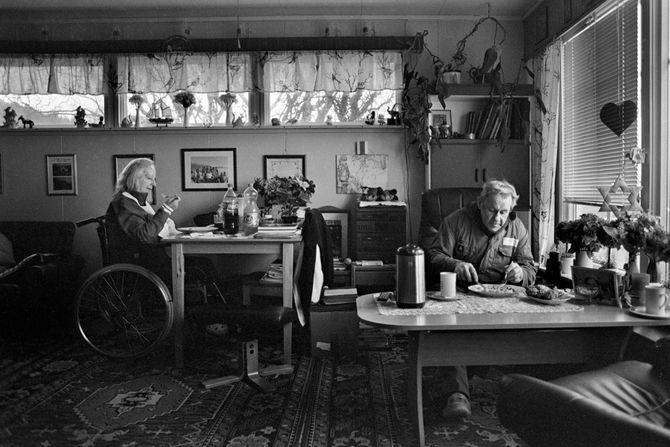 00596  09? 07.03.14  Tuss¿y? Tuss¿y ligger pŒ yttersida av Troms, og har en hŒndfull fastboende. Det er stor uenighet om hvor mange innbyggere det er pŒ ¿ya, og antallet varierer etter hvem av innbyggerne du sp¿r. Noen mener det er fem innbyggere, noen sier det er sju og andre igjen hevder de er ni. PŒ femtitallet var folketallet oppe i seksti, men gradvis har folk flyttet n¾rmere skole, jobb og en mer praktisk hverdag. Dette er en dokumentar om de som har valgt Œ bo pŒ Tuss¿ya.   Bildene er fotografert i 2014 og 2015.  Ekteparet Ragnvald og Olly Kristiansen spiser boknafisk.