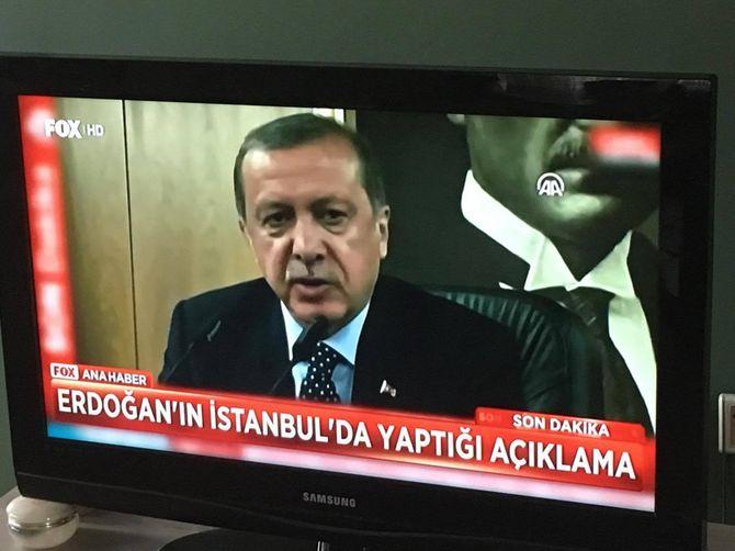 Erdogan snakker til tyrkiske medier foran bilde av Ataturk på Ataturk flyplass, natt til 16. juli. Hans første offentlige opptreden etter kuppforsøket.
