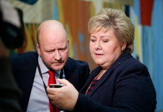Statsminister Erna Solberg (H) sjekker mobiltelefonen etter spørretimen onsdag, sammen med statssekretær Sigbjørn Aanes. Foto: Vidar Ruud / NTB scanpix