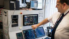 Scott Plimley viser fram den norske operatørkonsollen inne på avionikk-integrasjonstestanlegget, med det nyintegrerte systemet for å finne mobiltelefoner.