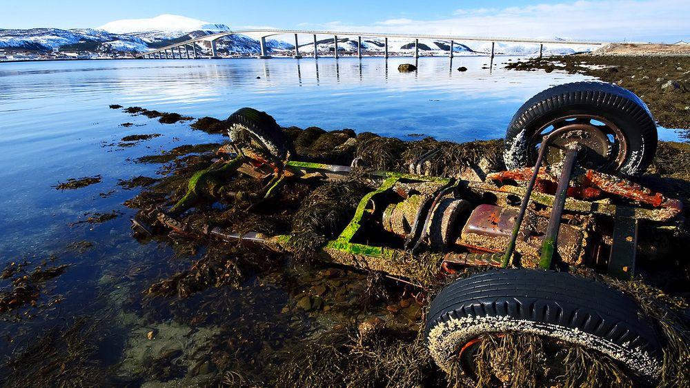 Et bilvrak ligger i fjæra ved Sortlandssundet i Vesterålen. Flere bilvrak kan bli liggende i naturen om ikke importerte biler omfattes av returordningen, advarer Autoretur.