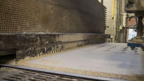 Ultrafint «mel» av kvernet glass glir sakte inn i de enorme ovnene, hvilende på en duk av glassfiber.
