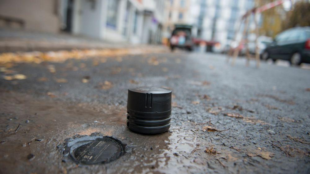 BAKKESENSOR: Disse sensorene skal gjøre 300 parkeringsplasser i Oslo smarte. Bildet viser to sensorer: En er allerede montert i bakken, mens den andre venter på å komme ned i asfalten.