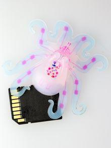 I stedet for kretskort og andre stive elektroniske komponenter bruker et pneutmatisk nettverk (rosa farge) som er bygget inn i robotens kropp og hyperelastiske aktuator-armer. SD-kortet viser størrelsen.