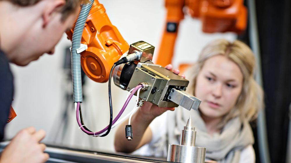 To studenter arbeider med en Chunk-griper på en ABB industrirobot.