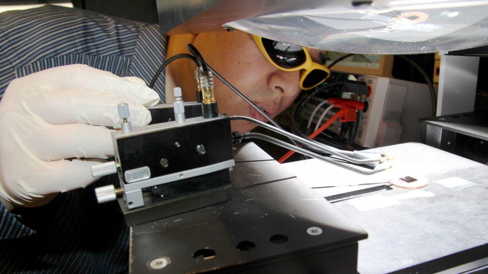 Testlaben: NTNU-forsker Xiaodong Yang på testlaben for solceller. Lampelyset ligner sollys, og han måler hvor god solcella er.