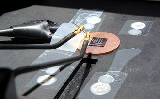 Testes: Ledningene til venstre er koblet til bak-elektroden, hvor strømmen går ut. Den kommer inn igjen gjennom probene på topp-elektroden. Inn og ut går det like mye strøm, ellers ville solcella tømmes for elektroner.