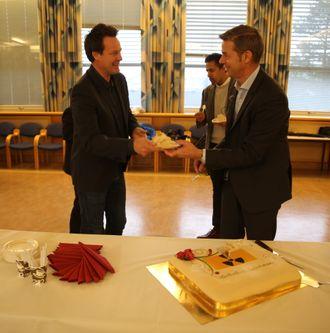 Administrerende direktør Nils Morten Huseby (t.h.) serverer atommerket kake til daglig leder Nils Bøhmer i Bellona for å feire at Venstre (representert med Abid Q. Raja i bakgrunnen) økte bevilgningene til Ifes atomopprydding med 20 millioner kroner i budsjettforliket.