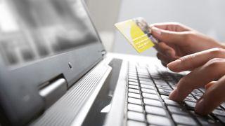 Person som taster inn kredittkortinformasjon på en laptop.